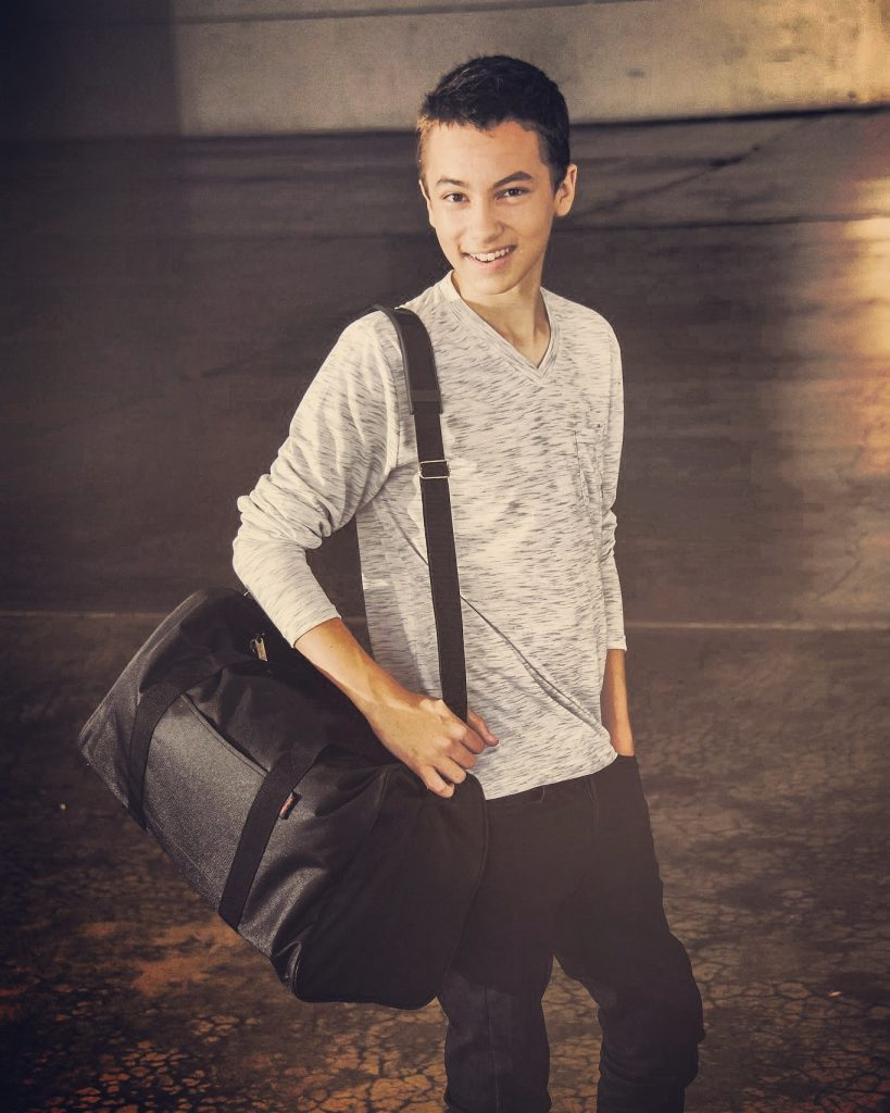 •Hayden Byerly, celebrity actor on The Fosters, wearing a duffle bag from his non-profit organization Hayden's Hope Totes, which benefits children who enter the foster system. Learn more at www.haydenshopetotes.org.